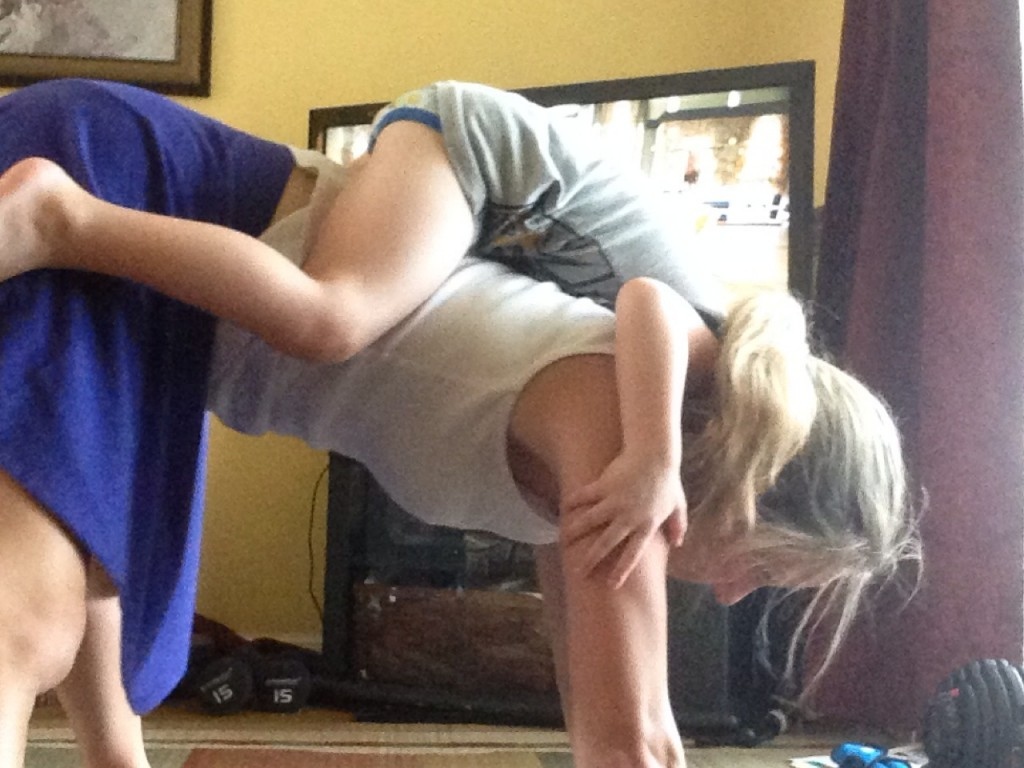 Mom working out child hanging on her